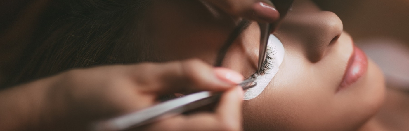 Close up of a beautician applying extended eyelashes to model.